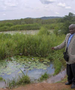 Father Namugera at the Fish Pond near the Trade School