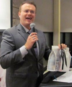 MC Justin Mazzatto auctions off a gift from Rinaldo's at the CANHAVE Dinner at Restaurant International, Algonquin College.